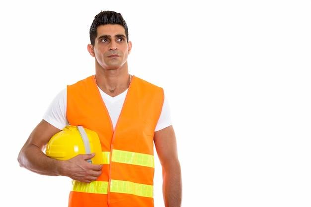 ヘルメットを保持している若い筋肉ペルシャ人建設労働者