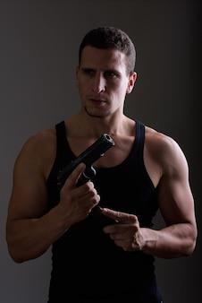 Молодой мускулистый персидский мужчина перезаряжает пистолет