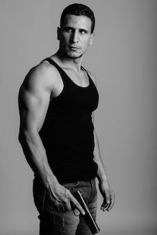 Молодой мускулистый персидский мужчина стоит и думает, держа пистолет у серой стены