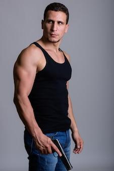 Молодой мускулистый персидский мужчина стоит и думает