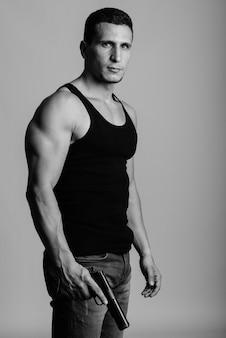 Молодой мускулистый персидский мужчина, держащий пистолет у серой стены