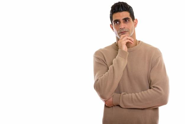 Молодой мускулистый персидский мужчина думает, глядя в сторону