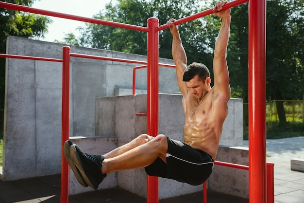 Young muscular shirtless caucasian man doing crunches on horizontal bar