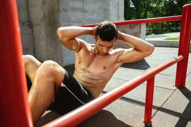 Young muscular shirtless caucasian man doing crunches on horizontal bar
