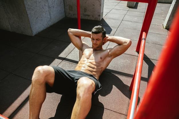 晴れた夏の日に遊び場で鉄棒でクランチをしている若い筋肉質の上半身裸の白人男性。上半身を屋外でトレーニングします。スポーツ、トレーニング、健康的なライフスタイル、幸福の概念。