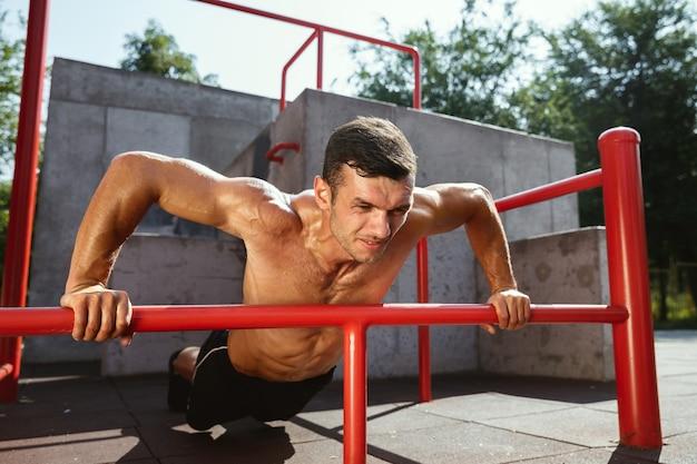 Giovane uomo caucasico senza camicia muscolare che fa pull-up sulla barra orizzontale