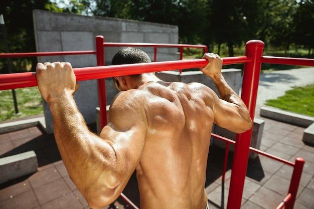 Молодой мускулистый кавказский мужчина без рубашки делает подтягивания на турнике на детской площадке в солнечный летний день. тренирует верхнюю часть тела на открытом воздухе. понятие спорта, тренировки, здорового образа жизни, благополучия.