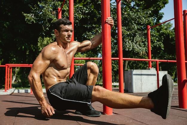 Giovane uomo caucasico senza camicia muscolare che fa squat vicino alla barra orizzontale al parco giochi nella soleggiata giornata estiva. allenamento della parte inferiore del corpo all'aperto. concetto di sport, allenamento, stile di vita sano, benessere.