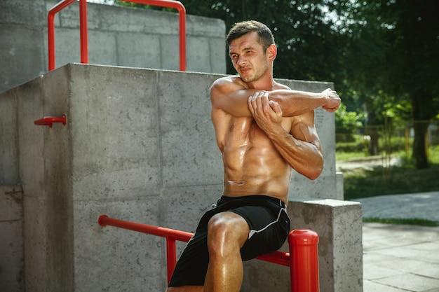 Молодой мускулистый кавказский мужчина без рубашки делает упражнения на растяжку на детской площадке в солнечный летний день. тренирует верхнюю часть тела на открытом воздухе. понятие спорта, тренировки, здорового образа жизни, благополучия.