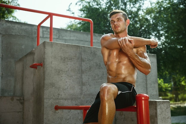 Young muscular shirtless caucasian man doing stretching exercises at playground in sunny summer's day.