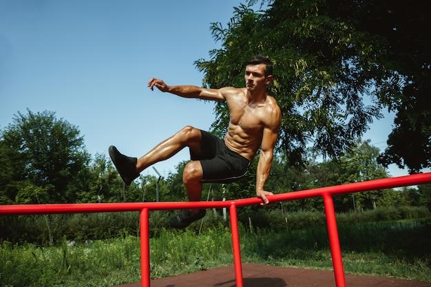 Молодой мускулистый кавказский мужчина без рубашки прыгает над турником на детской площадке в солнечный летний день. тренирует верхнюю часть тела на открытом воздухе. понятие спорта, тренировки, здорового образа жизни, благополучия.