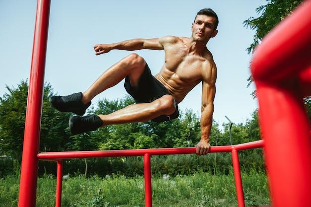 Молодой мускулистый кавказский мужчина без рубашки прыгает над турником на детской площадке в солнечный летний день