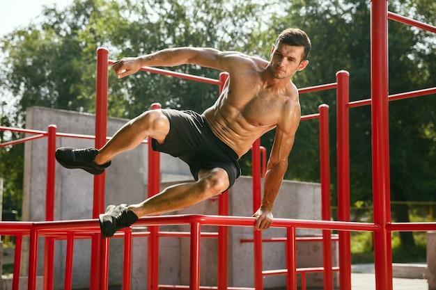 鉄棒の上をジャンプする若い筋肉質の上半身裸の白人男性