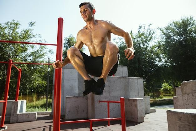 Giovane uomo caucasico senza camicia muscolare che salta sopra la barra orizzontale al parco giochi nella soleggiata giornata estiva. allenare la parte superiore del corpo all'aperto. concetto di sport, allenamento, stile di vita sano, benessere.