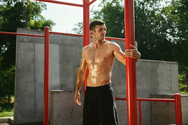 Young muscular shirtless caucasian man while doing his workout on horizontal bars at playground in sunny summer's day. training his body outdoors. concept of sport, healthy lifestyle, wellbeing.