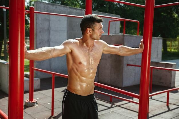 Giovane uomo caucasico senza camicia muscolare mentre fa il suo allenamento su barre orizzontali al parco giochi nella soleggiata giornata estiva. allenare il suo corpo all'aperto. concetto di sport, stile di vita sano, benessere.