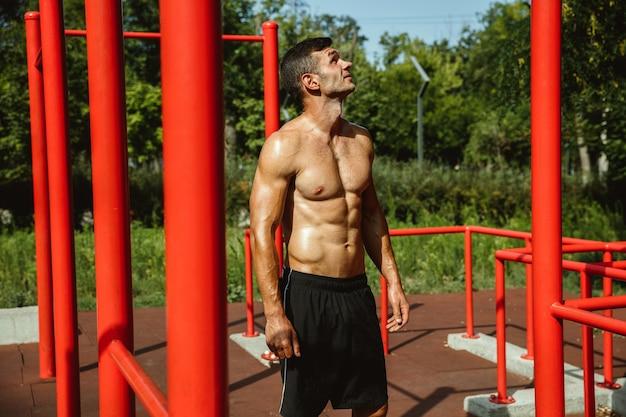 Giovane uomo caucasico senza camicia muscolare mentre fa il suo allenamento su barre orizzontali al parco giochi nella soleggiata giornata estiva