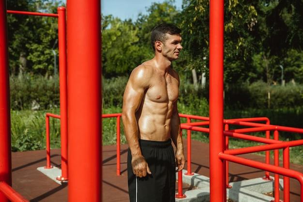 Молодой мускулистый кавказский мужчина без рубашки во время тренировки на турниках на детской площадке в солнечный летний день. тренирует свое тело на открытом воздухе. понятие спорта, здорового образа жизни, благополучия.