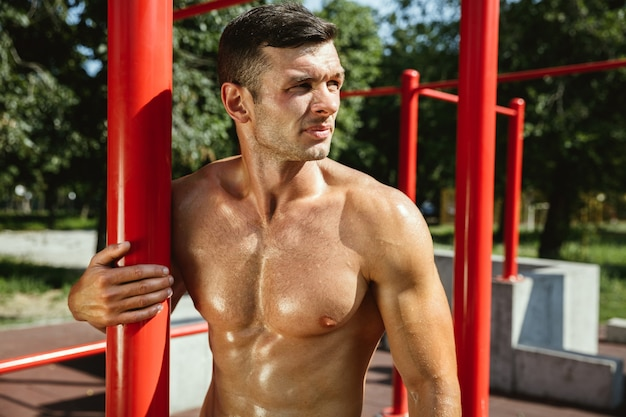 화창한 여름 날에 놀이터에서 가로 막대에 그의 운동을하는 동안 젊은 근육 shirtless 백인 남자. 야외에서 그의 몸을 훈련. 스포츠, 건강한 라이프 스타일, 웰빙의 개념.