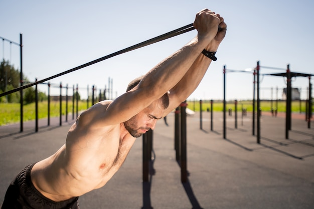 Young muscular shirtless man bending forwards while stretching resistance band during workout outdoors