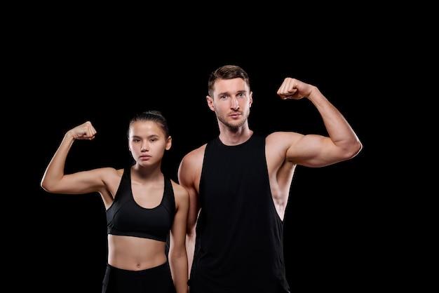 Молодой мускулистый спортсмен и симпатичная женщина в спортивной одежде, демонстрирующая свою силу стоя