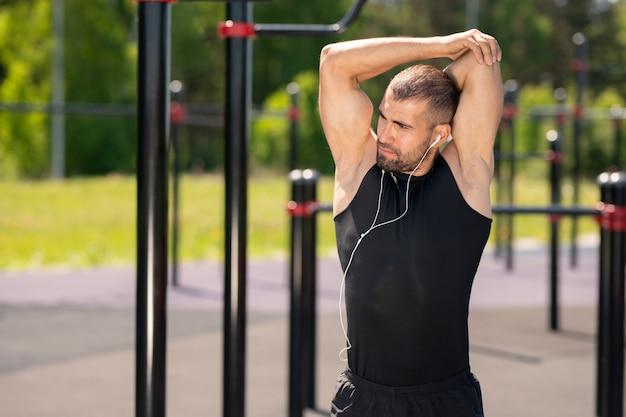 Молодой мускулистый спортсмен в черном спортивном костюме делает упражнения для рук, стоя на спортивной площадке на улице