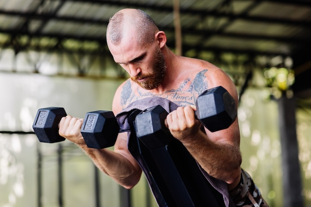 激しい運動をしている若い筋肉の入れ墨の強い筋肉ひげを生やしたヨーロッパ人