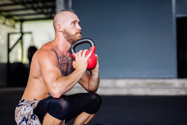 Молодой мускулистый татуированный сильный мускул бородатый европейец делает тяжелые упражнения
