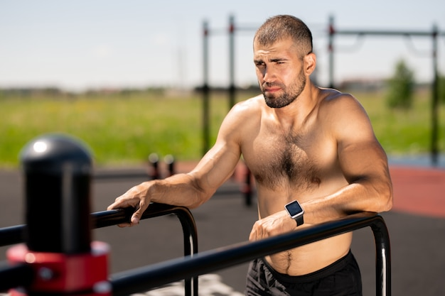 屋外でエクササイズしようとしながらスポーツ施設のバーで保持している若い筋肉トップレスボディービルダー