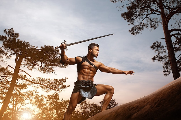 Young muscular warrior with a sword at the mountains