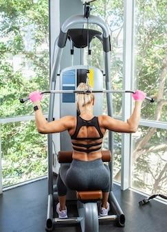 체육관에서 위도 기계에서 풀다운 운동을 하 고 젊은 근육 질의 여자. 뒷모습