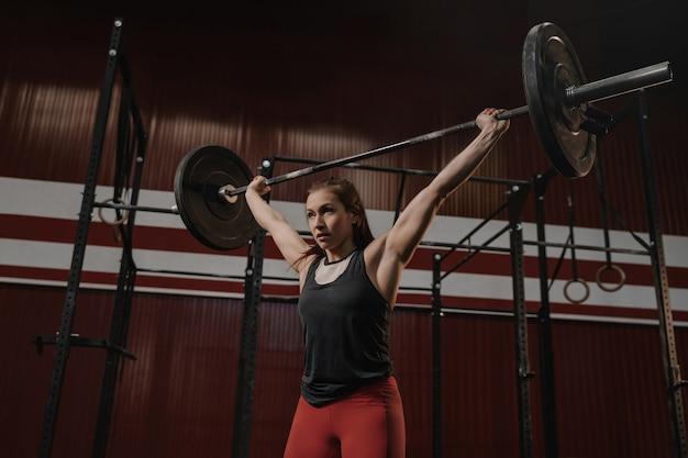 ジムでウェイトリフティングの練習をしている若い筋肉の女性。ジムで重いウェイトを持ち上げる女性アスリートにフィットします。