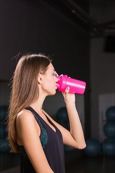 ジムでスポーツ栄養を飲む若い筋肉の女性。