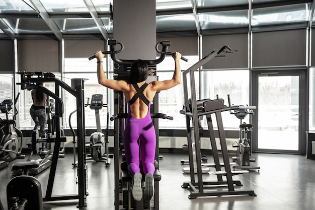 Young muscular woman practicing in gym with equipment