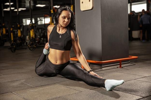 Giovane donna muscolare che pratica in palestra con attrezzature