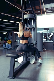 Young muscular woman practicing in gym with the weights