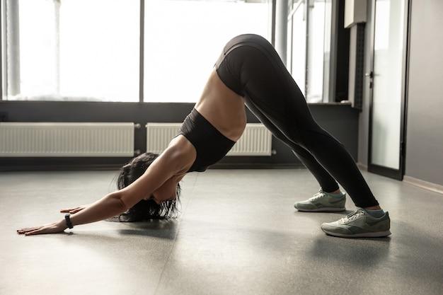 Giovane donna muscolare che pratica in palestra