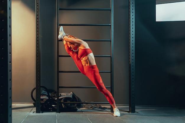 Молодая мускулистая женщина, практикующая в тренажерном зале