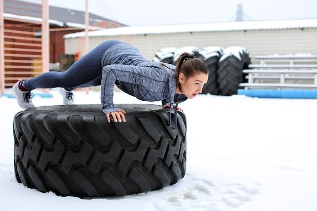 무거운 타이어, 야외에서 훈련하는 젊은 근육 질 여자