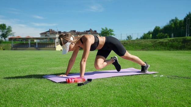 晴れた夏の日にマットの上で登山運動をしている白い帽子をかぶった若い筋肉の女性。新鮮な緑の芝生のスタジアムフィールドでコア筋肉をトレーニングするゴージャスな女の子。トレーニングの概念。