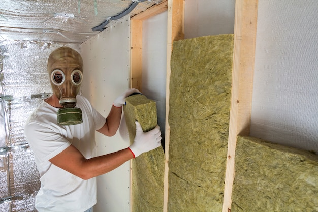 Young muscular worker in gas mask insulating rock wool staff in wooden frame for future house walls for cold and heat barrier. comfortable warm home, economy, construction and renovation concept.