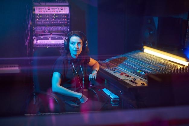 音楽キーボードに座ってスタジオで曲を書いているヘッドフォンの若い音楽プロデューサー