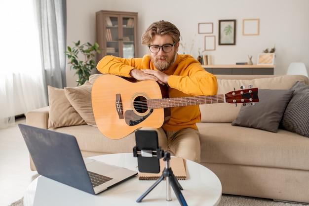Молодой учитель музыки разговаривает со своей аудиторией во время онлайн-урока игры на гитаре, сидя на диване перед камерой смартфона