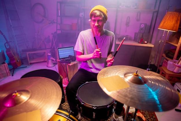자신의 차고 또는 스튜디오에서 개별 리허설을하는 동안 새로운 음악을 만드는 동안 나지만 심벌즈를 이길 젊은 음악가