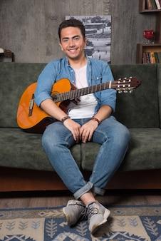 美しいギターを持ってソファに座っている若いミュージシャン。高品質の写真