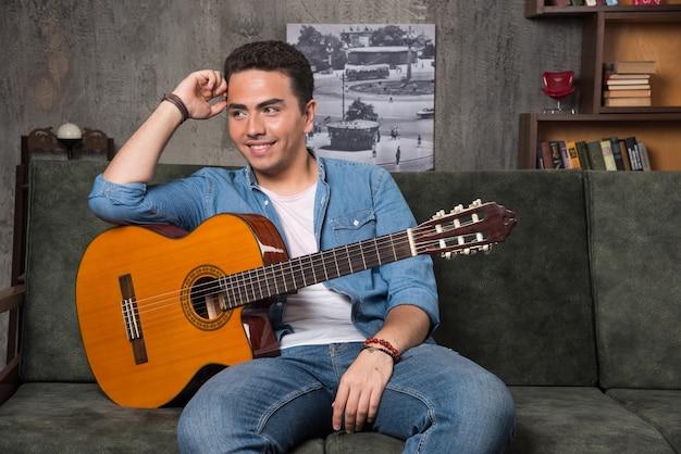 Giovane musicista che tiene una bella chitarra e che si siede sul sofà. foto di alta qualità