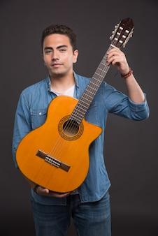 Giovane musicista che tiene chitarra su sfondo nero