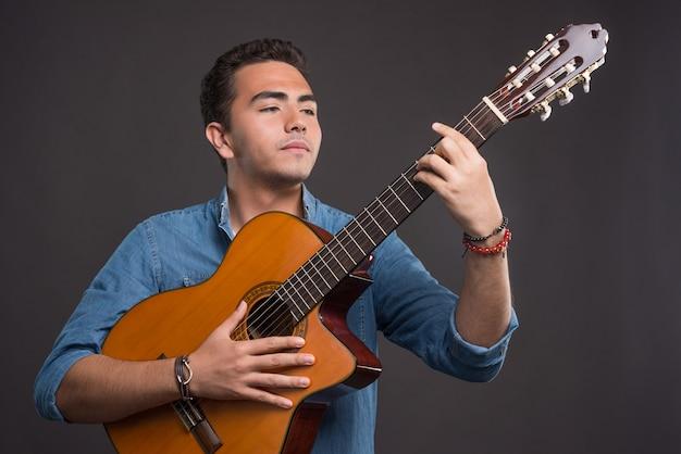 Молодой музыкант держит гитару на черном фоне