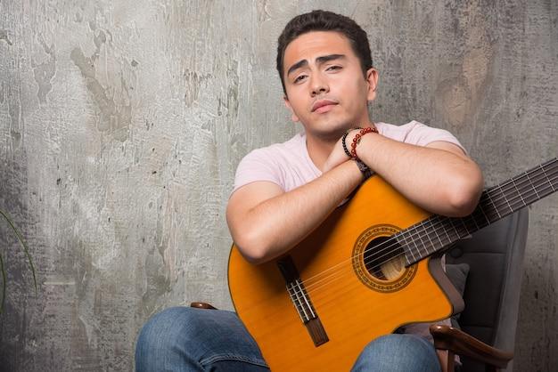 Молодой музыкант держит гитару на мраморном фоне
