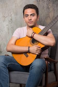Молодой музыкант обнимает гитару на мраморном фоне